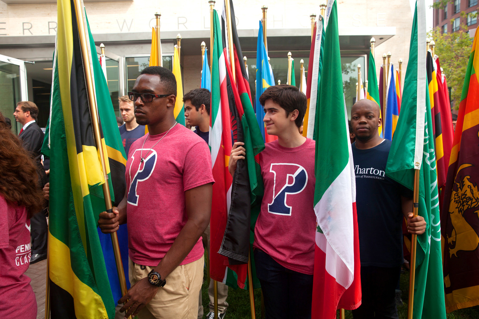Students holding flags, standing in front of Perry World House