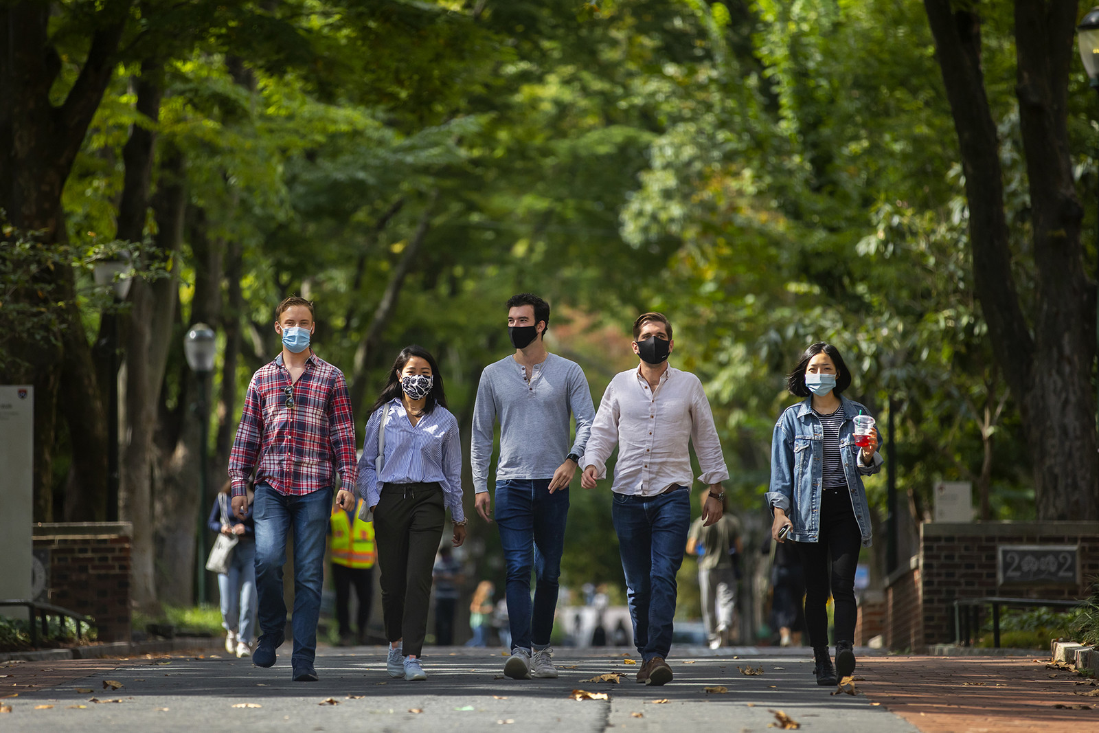 five students walking down locust walk with masks
