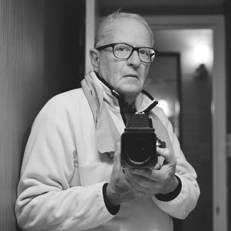 Black and white photo of Arthur Tress taking self portrait in mirror with a camera.
